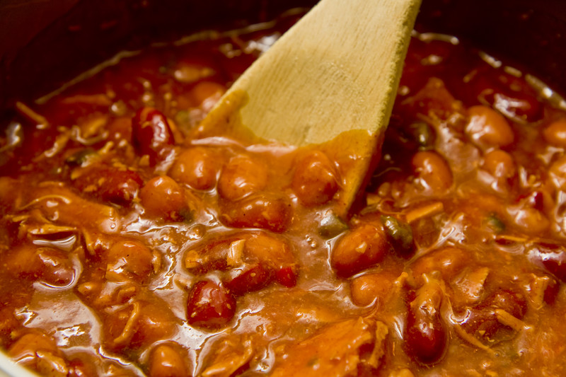 A wooden spoon stirring chili con carne.